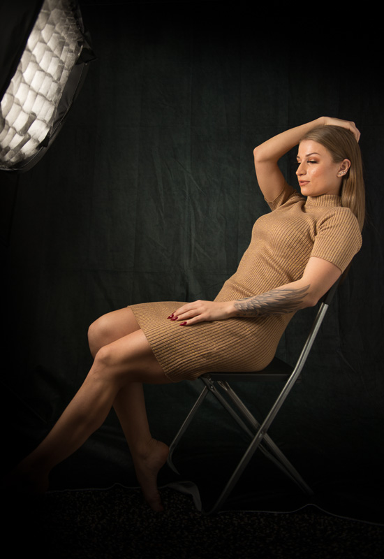 model sitting in front of a softbox during a fashion, portrait photoshoot.